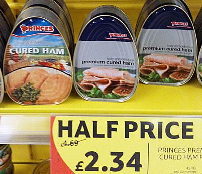 Canned cured ham for half price on shelf in a supermarket