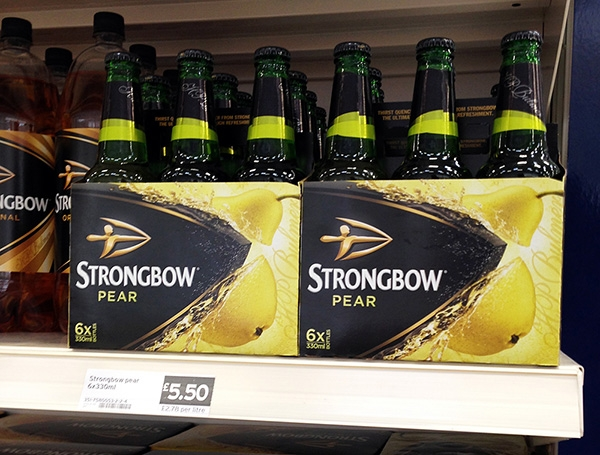Strongbow pear cider bottles in carry cases on shelf